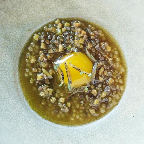 Ein in geröstetem Knochenmark sanft gegartes Wachtelei mit gepökeltem Hammelfleisch und verkohlten Zwiebeln